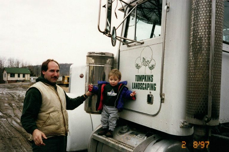 Mark Tompkins with young son on truck steps.